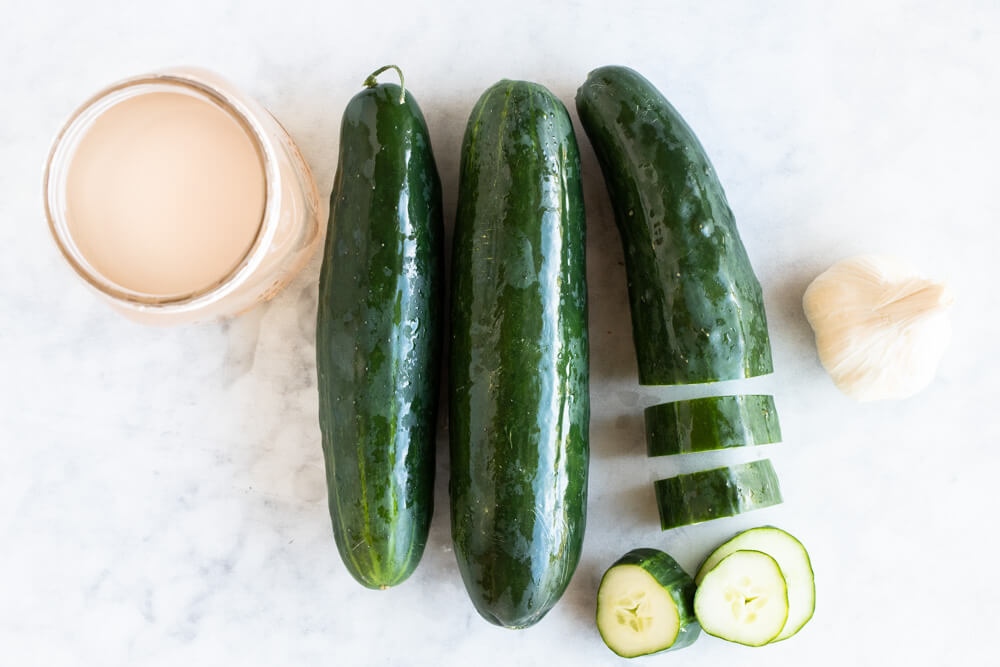 three cucumbers and garlic on kitchen counter