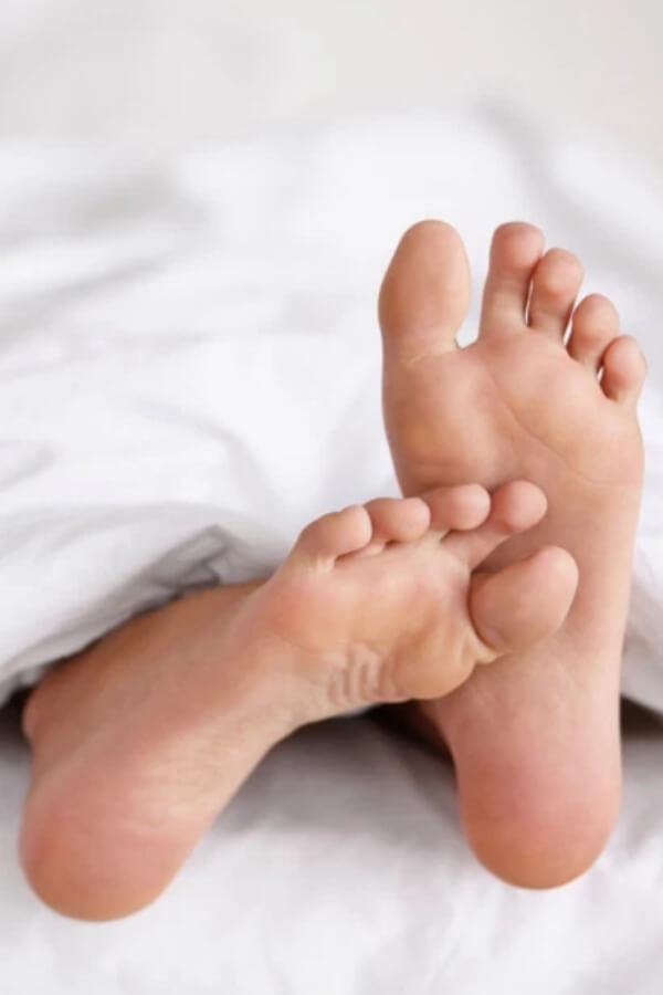 feet peeking out from under blanket