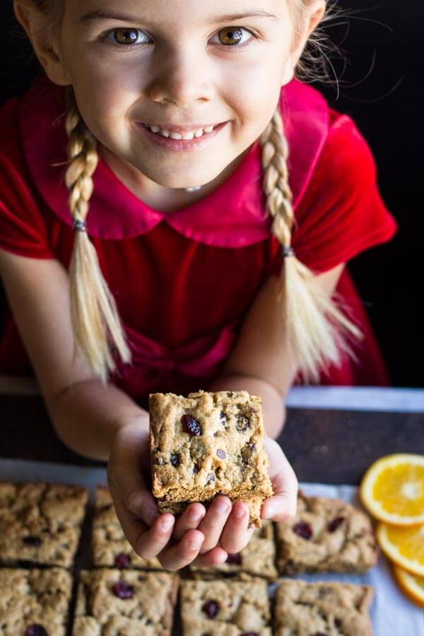 young child holding Orange Cranberry Chocolate Chip Cookie Bars