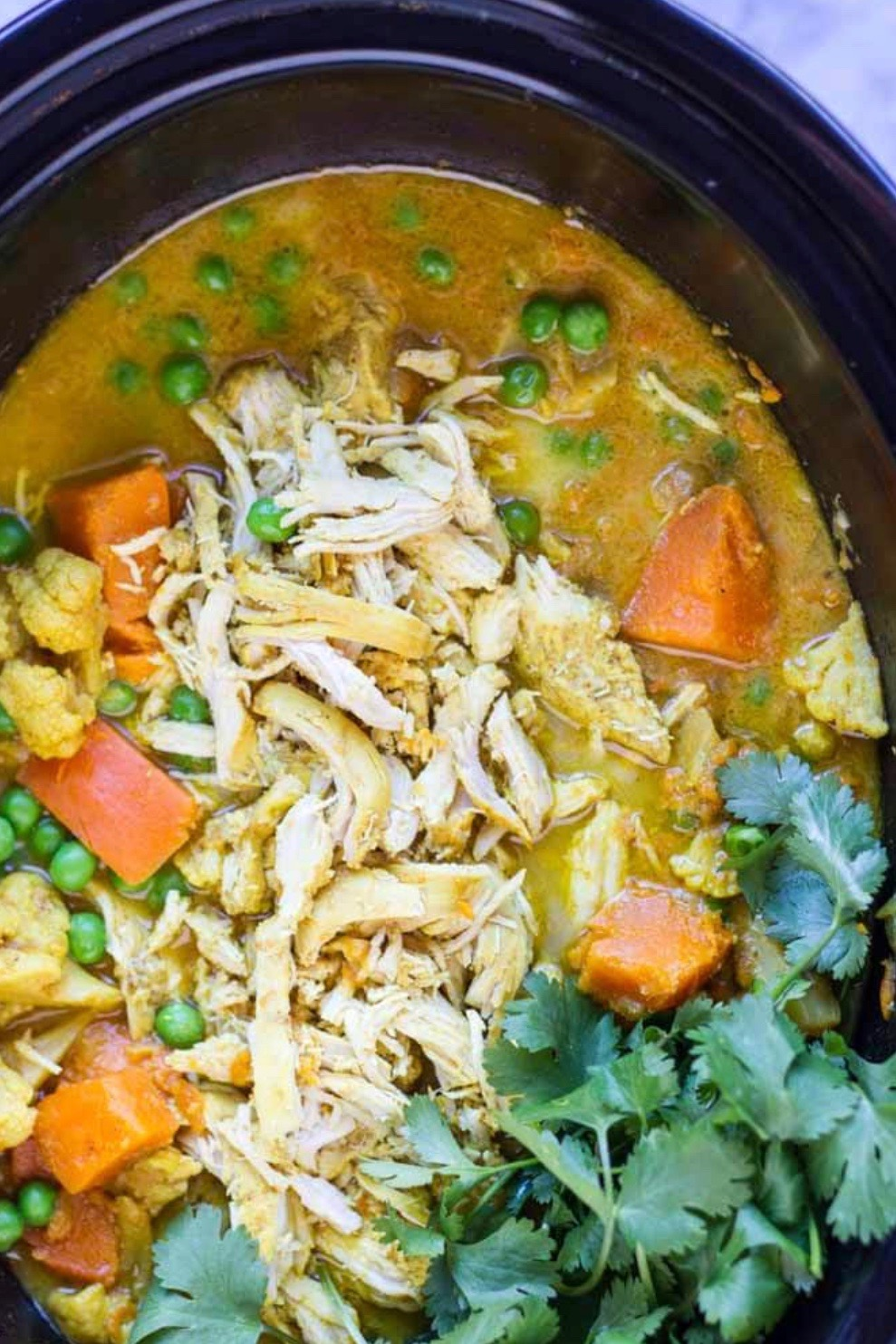 slowcooker with chicken curry in it