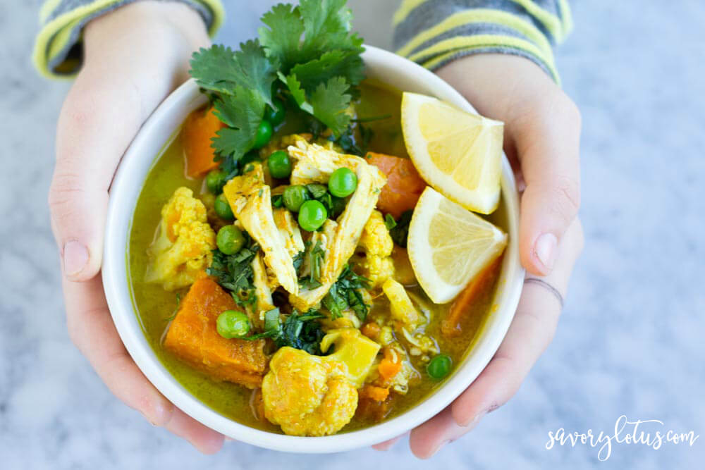 hands holding a white bowl with curry