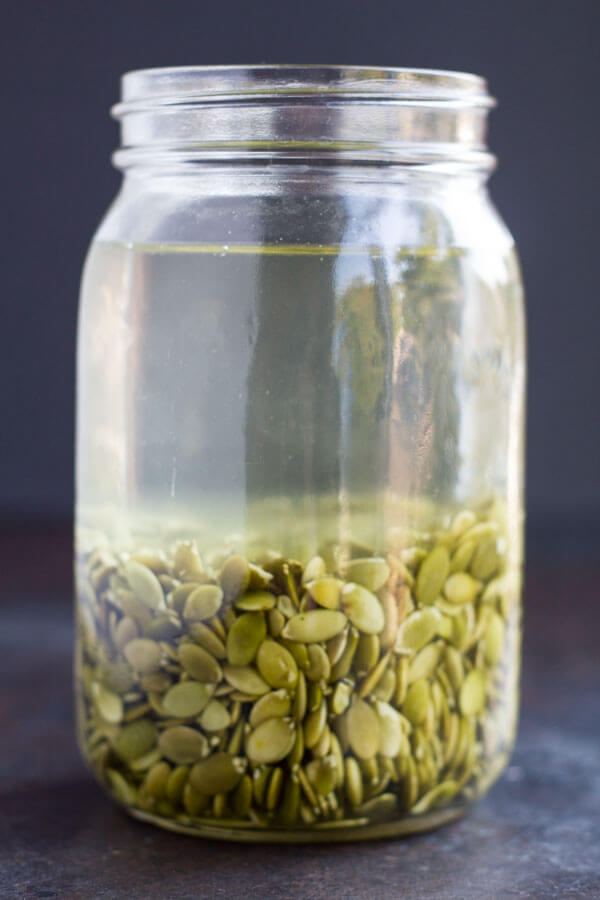 jar with pumpkin seeds soaking in it