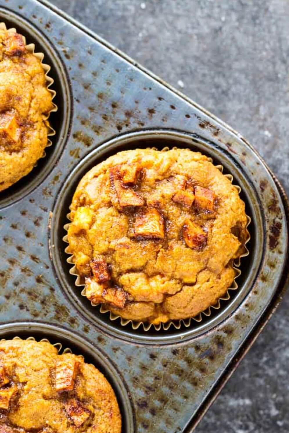 close up of an orange muffin with apples chunks on top