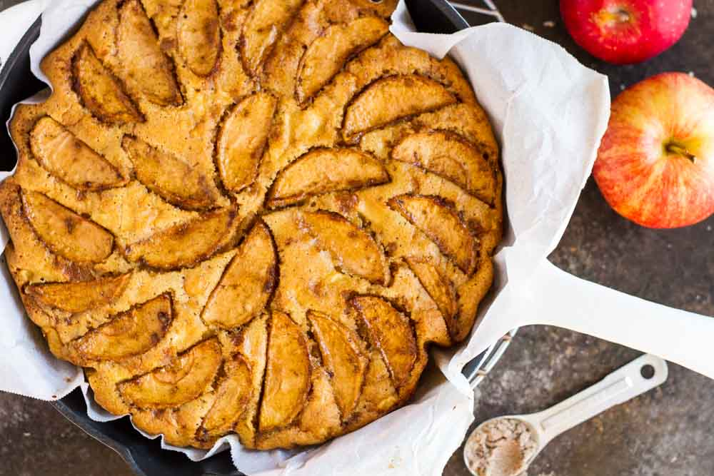 Cardamom Apple Cake in skillet with apples next to it