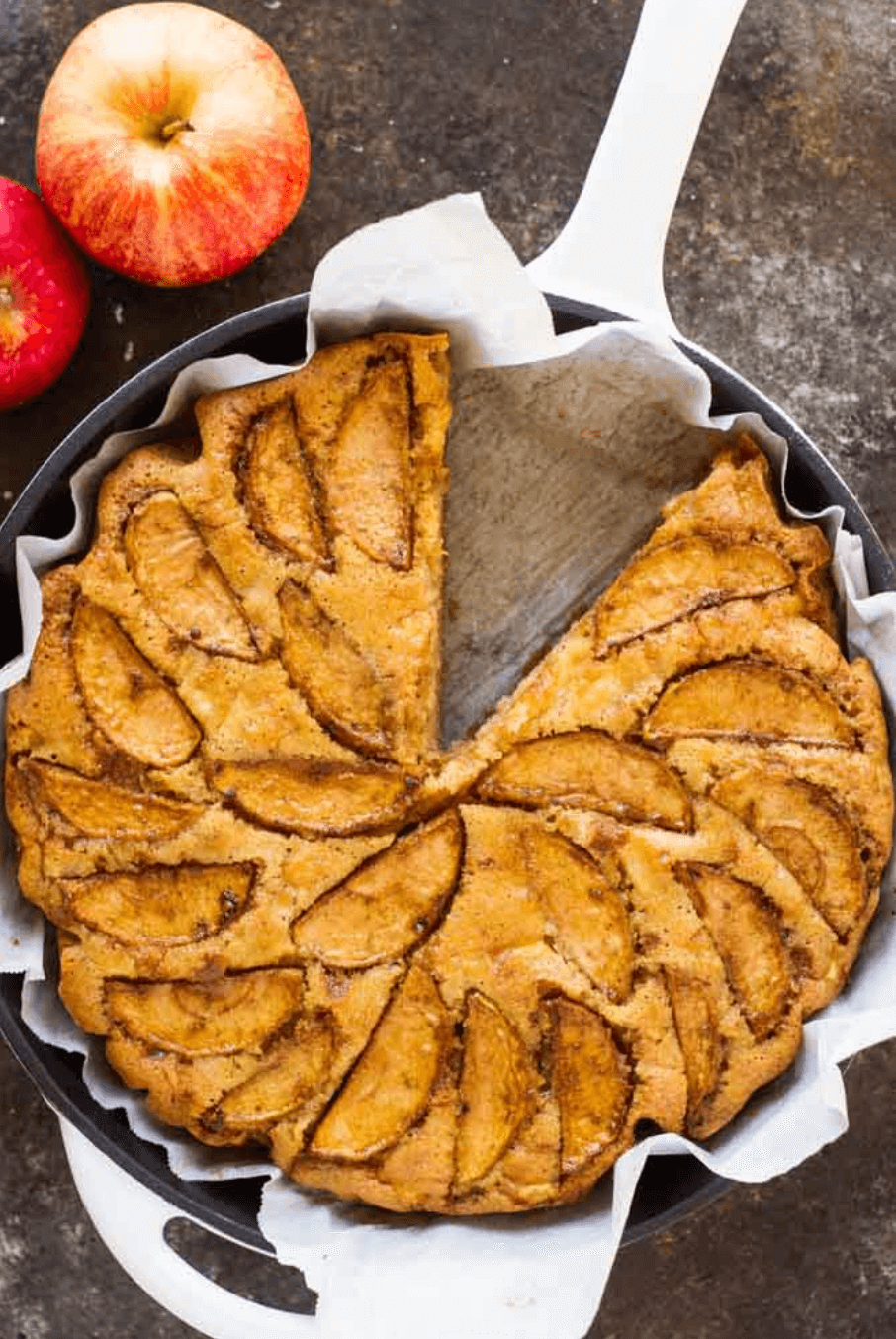 cardamon apple cake in skillet with one slice cut out