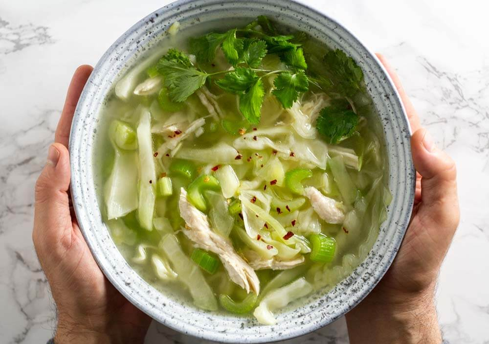 |cabbage, celery, bone broth soup in white bowl held in hands