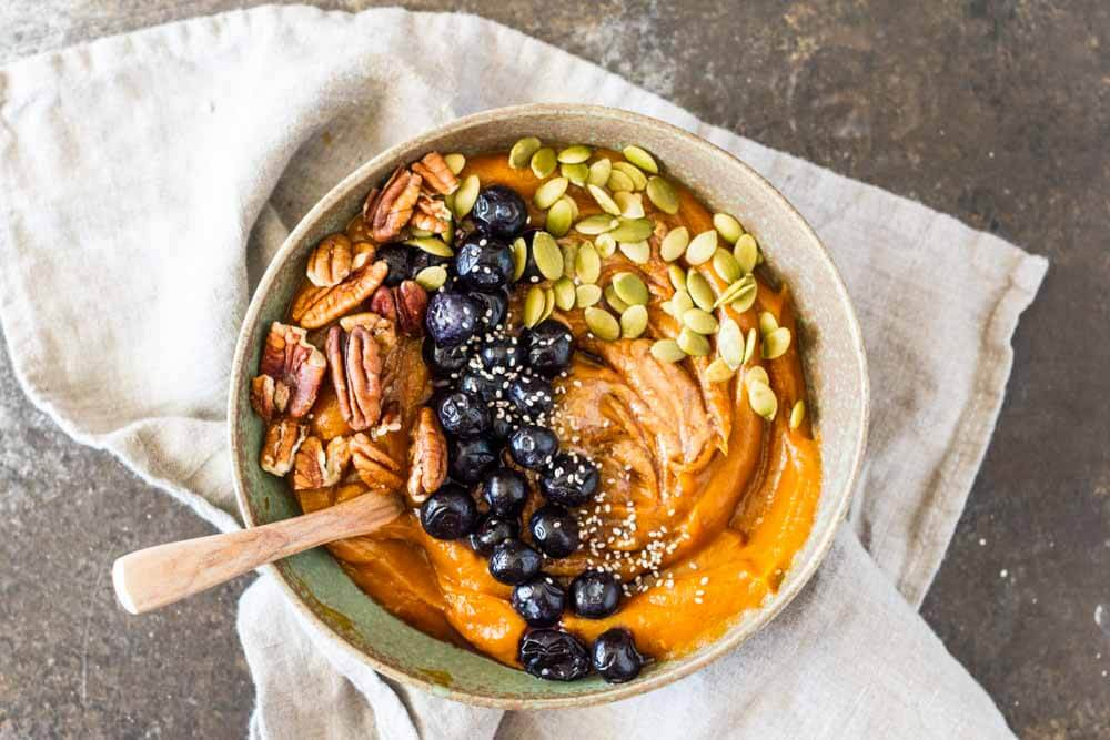 Simple Sweet Potato Breakfast Bowl (gluten free, grain free) in a bowl on a napkin with pecasn, blueberries, and pumpkin seeds| www.savorylotus.com