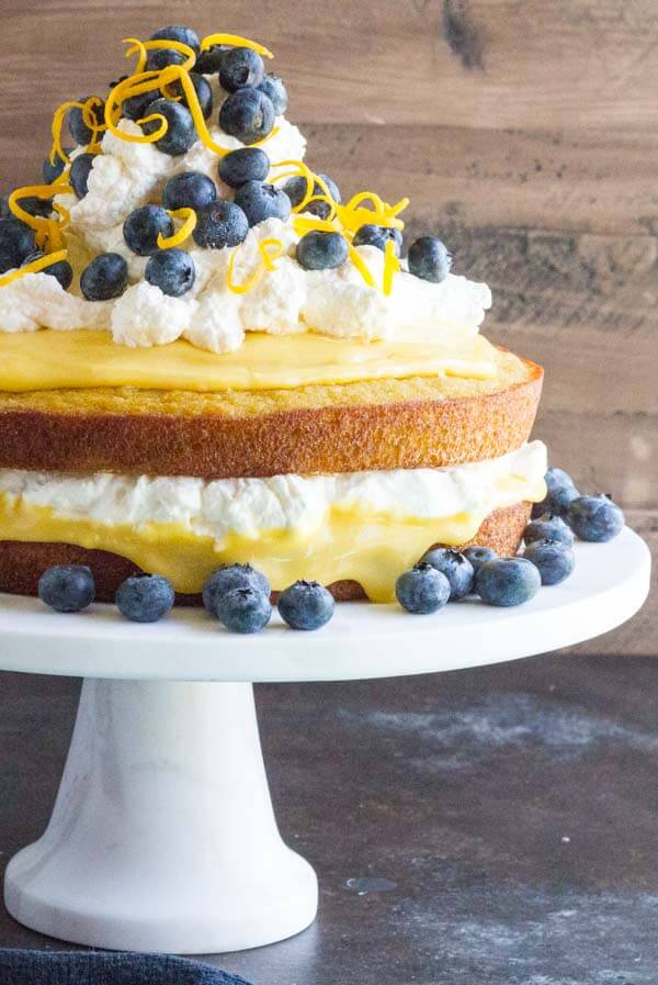 whipped cream and blueberries on top of a cake