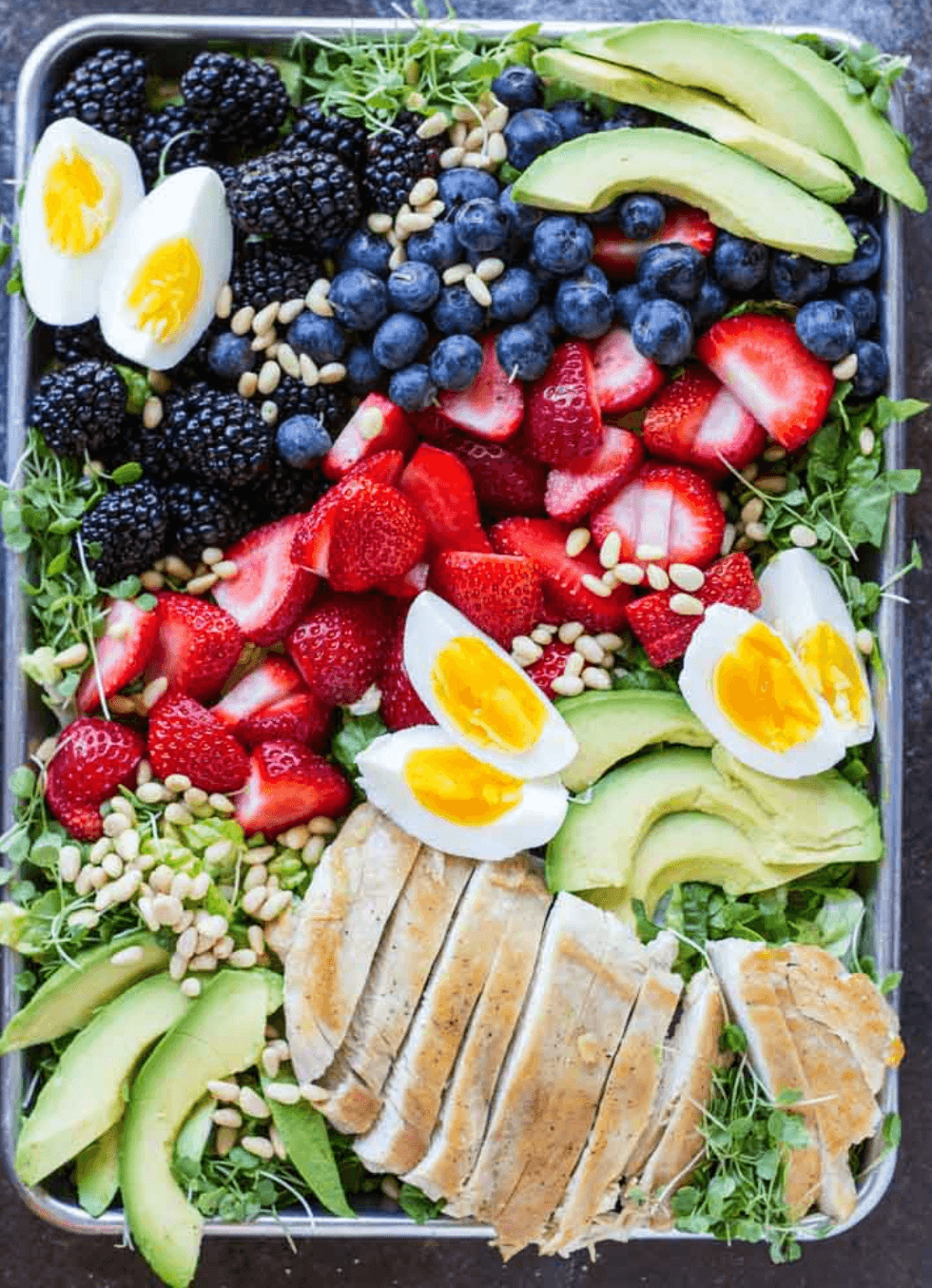 metal baking tray with avocado berry chicken salad