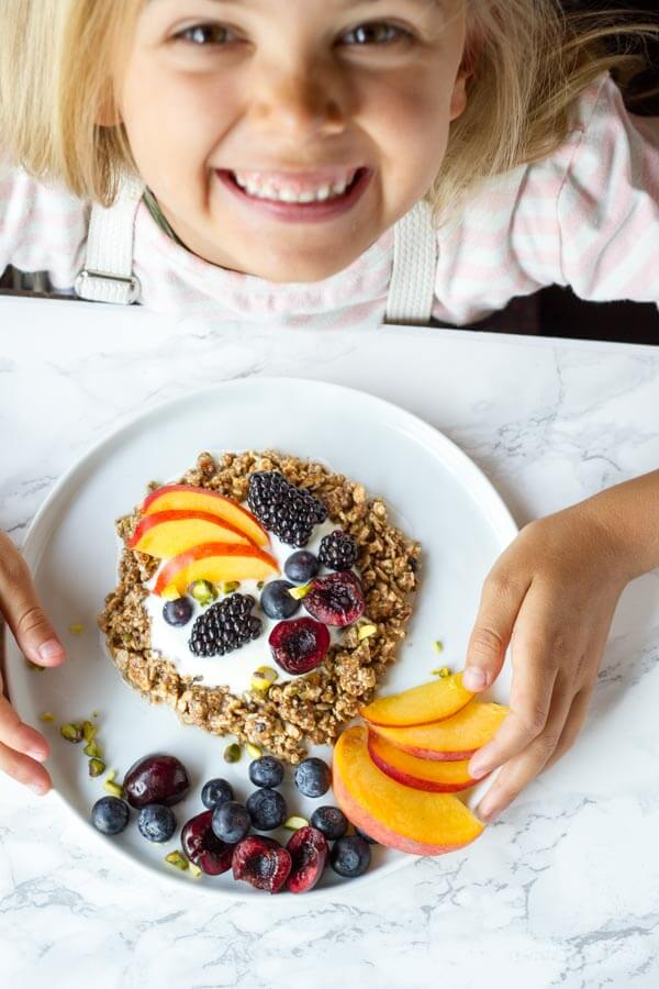 small child holding white plate of No Bake Granola Breakfast Cookies