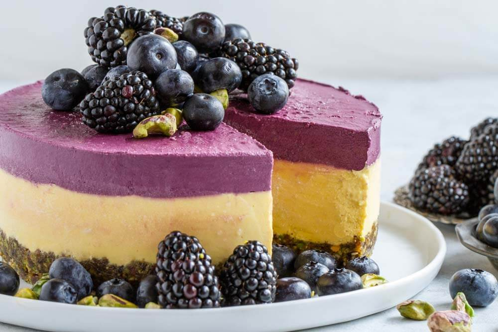 whole Mango Blackberry Cheesecake with blackberries and blueberries on top