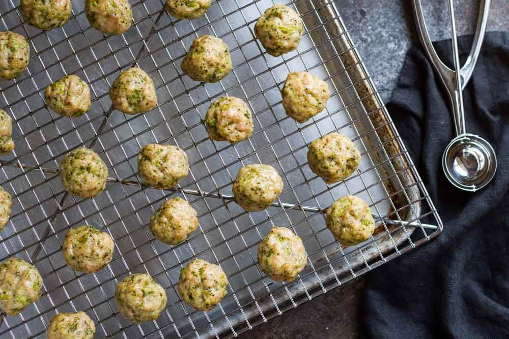 Easy Broccoli Chicken Meatballs on baking tray with black napkin next to them