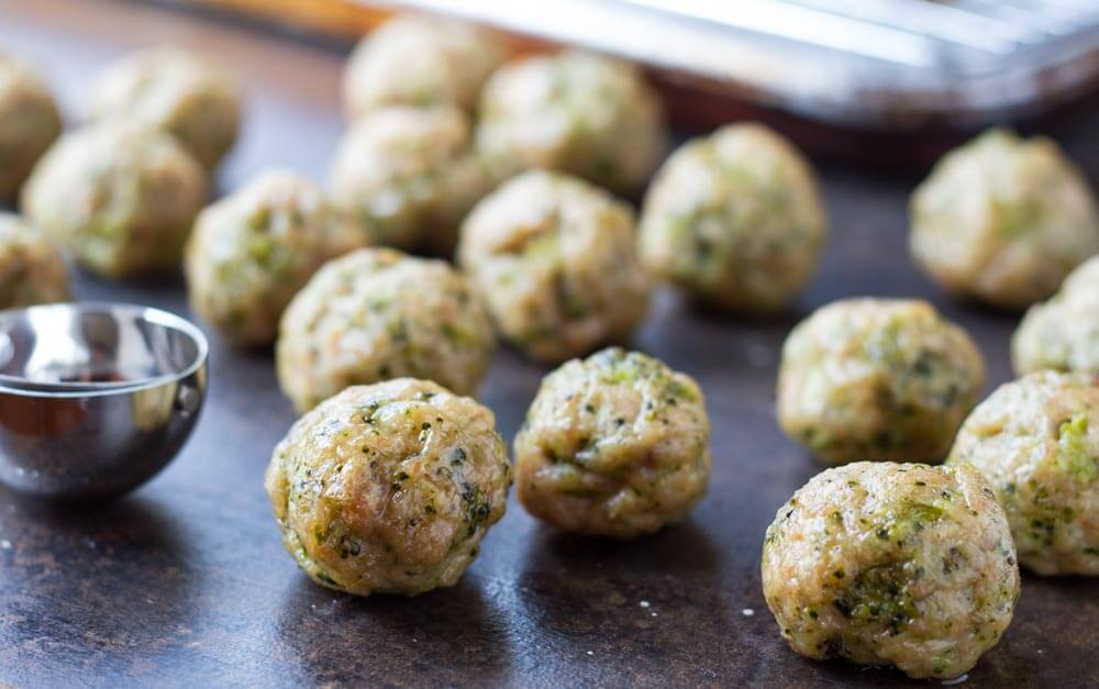 several Broccoli Chicken Meatballs with scooper next to them