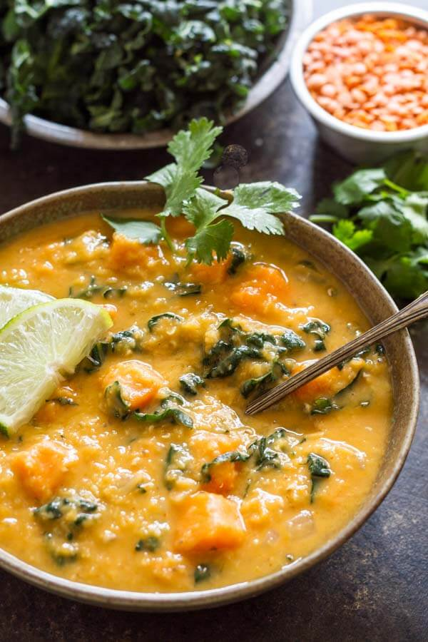 Thai Red Curry Lentil Soup in green bowl with lime wedge on top