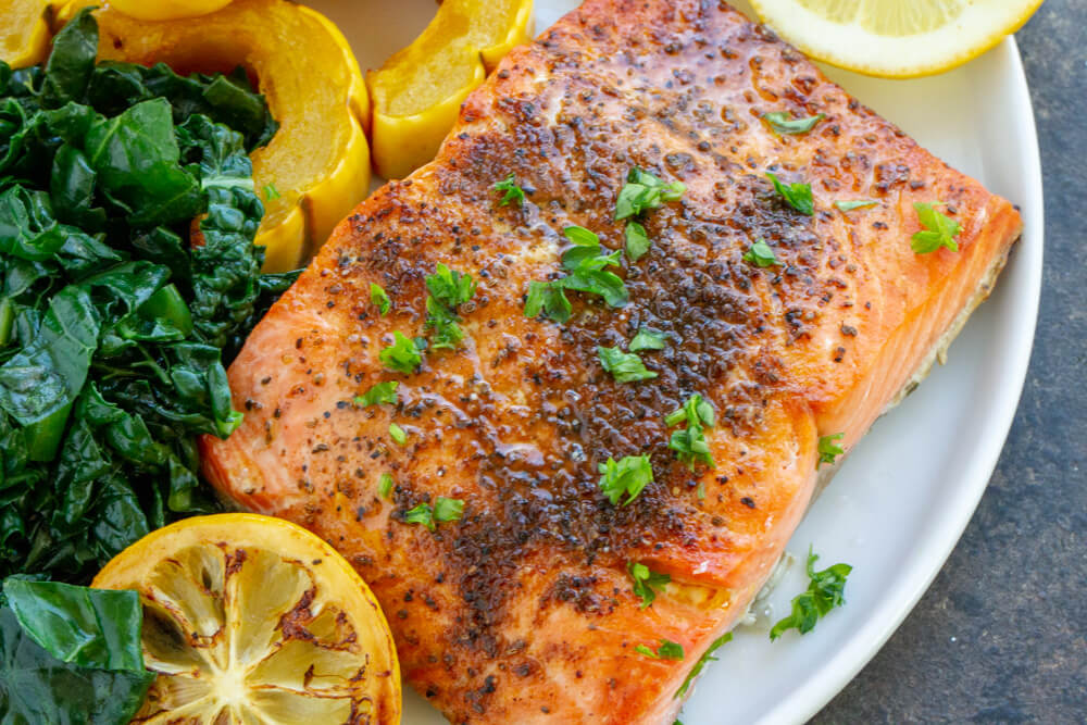 Broiled Salmon on white plate with a side of greeens