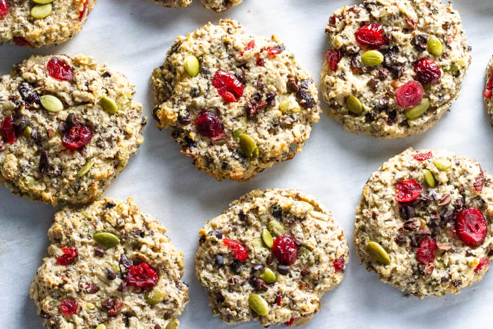 six cookies with dried cranberries and nuts on parchment paper