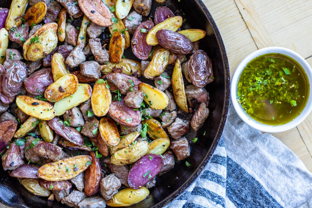 Steak Bites with Garlicky Potatoes  in a cast iron skillet