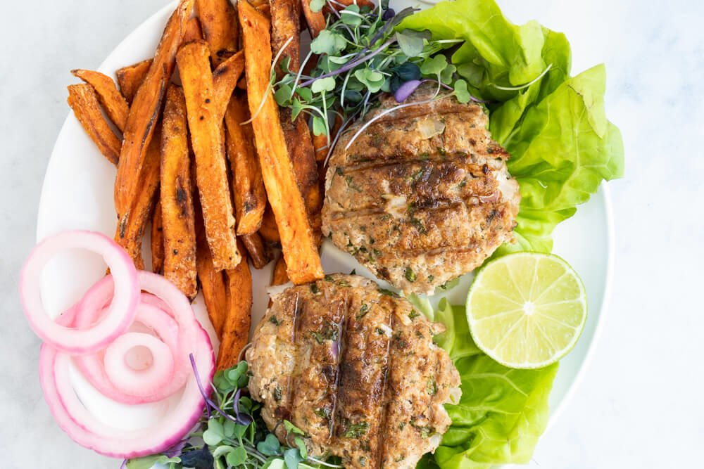 Chili Lime Chicken Burgers on white plate with sweet potato fries