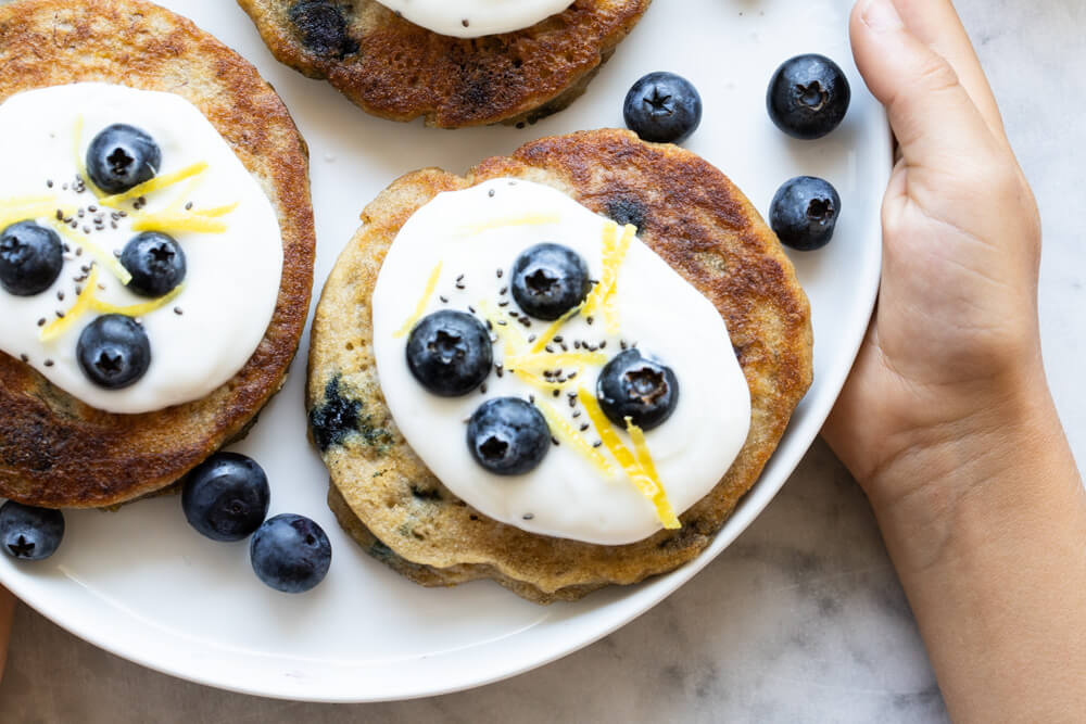 close up of a blueberry pancake with yogurt and berries on top