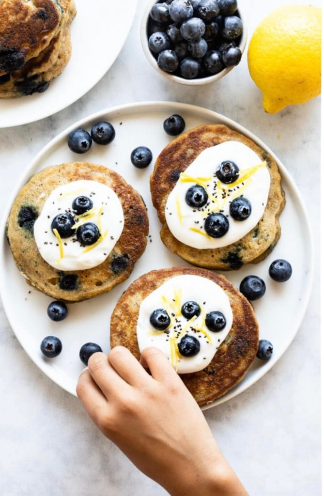 white plate with blueberry pancakes and yogurt