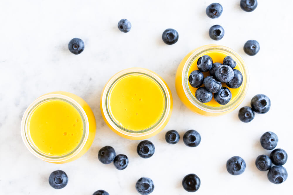 three jars of mango pudding with blueberries on top