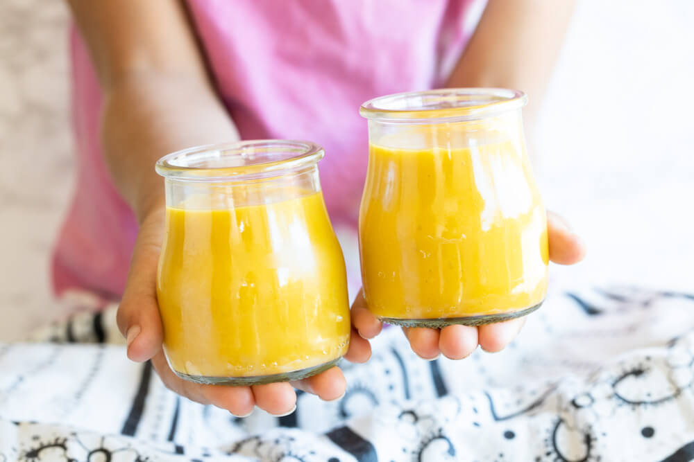 hands holding two jars of yellow pudding