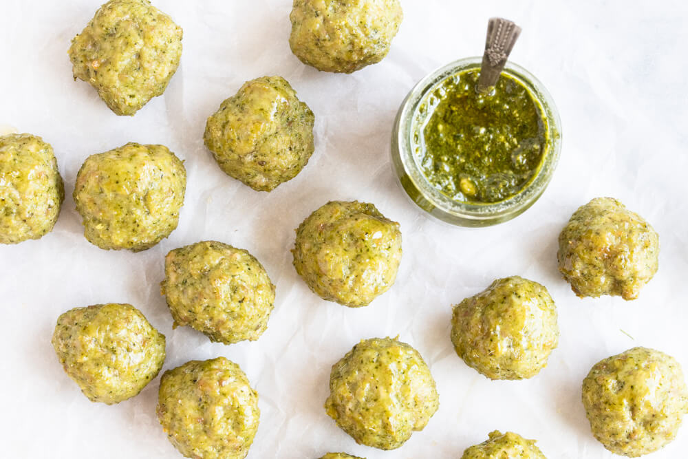meatballs on white paper with jar of pesto