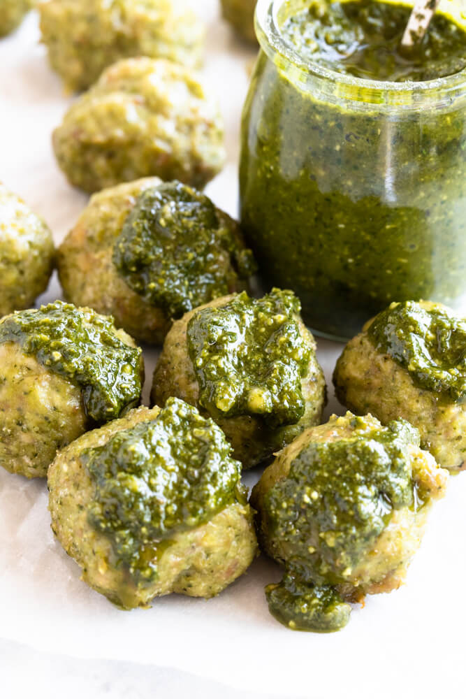 meatballs covered in pesto with a jar of pesto next to them