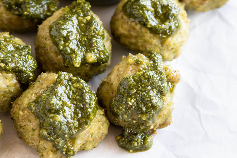 close up of meatballs with pesto on them