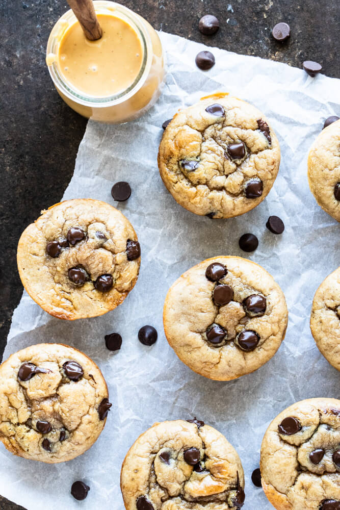 peanut butter chocolate chip muffins on white parchment paper and a jar of peanut butter