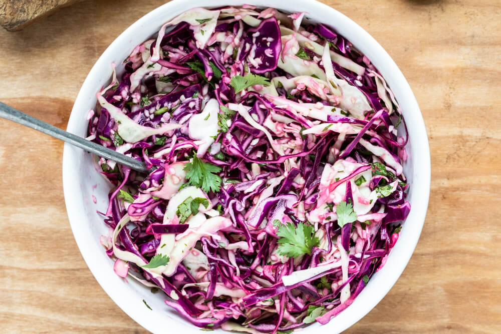 close up of red b=cabbage and cilantro slaw in white bowl