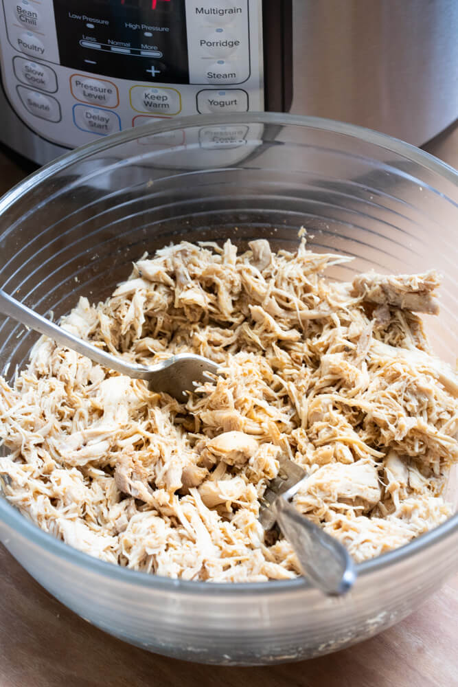 glass bowl with shredded chicken and two forks