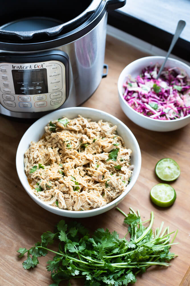 shredded chicken in white bowl next to an Instant Pot