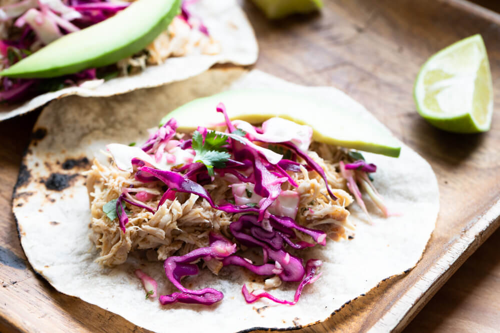 shredded chicken taco with red cabbage on top