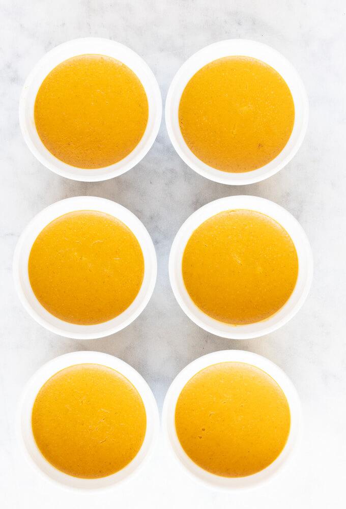 six white ramekins of pumpkin custard