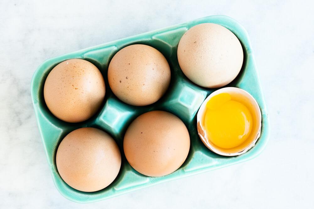 six eggs in a green carton