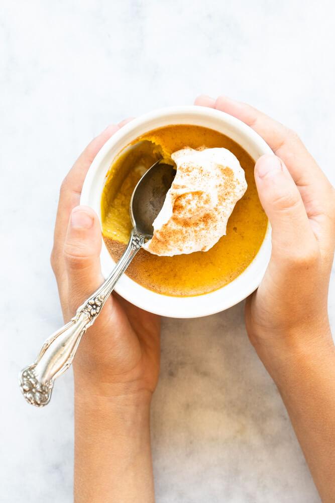 hands holding small bowl of pumpkin custard