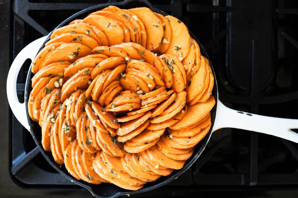 uncooked sweet potato slices in skillet