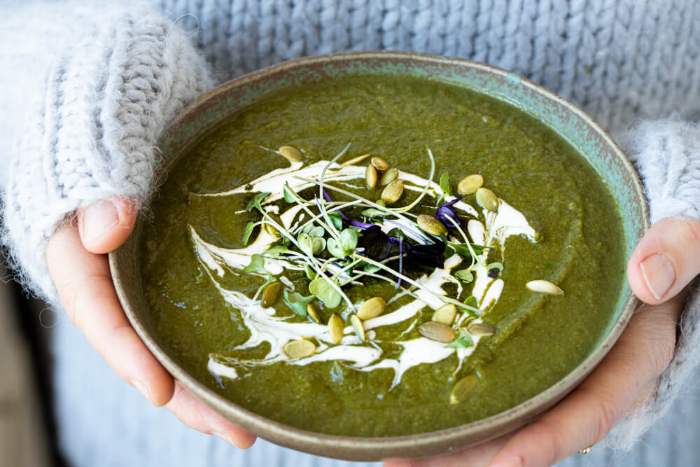 hands holding green bowl with detox green soup