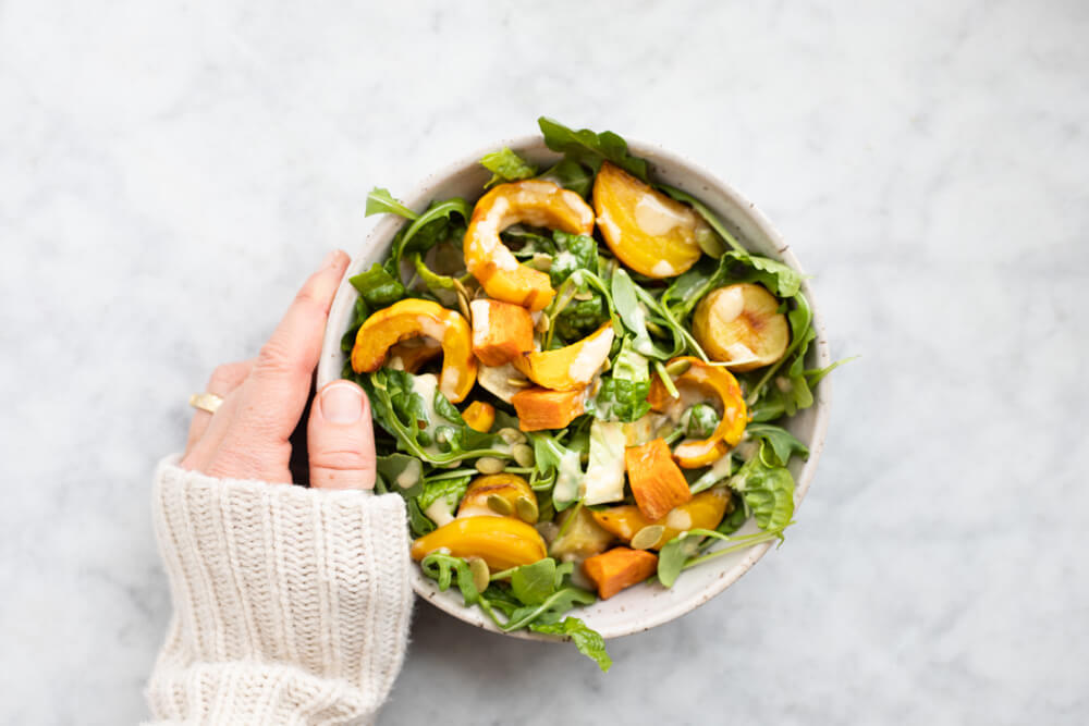 hand holding white bowl with winter salad